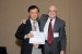"Dr. Nagib Callaos, General Chair, giving Prof. Shigehiro Hashimoto the best paper award certificate of the session ""Biological Engineering."" The title of the awarded paper is ""Responses of Cells to Flow in Vitro."""
