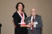 "Dr. Nagib Callaos, General Chair, giving Dr. Ruth Bergman award in appreciation for delivering a Great Plenary Keynote Address on ""Enterprise IT as Knowledge Keeper"""